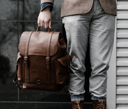 muž drží hnědý kožený pánský batoh
