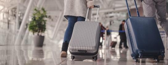 Cestující na letišti táhne šedý skořepinový kufr na kolečkách